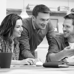 36168113 - business people smiling together while looking at laptop in office